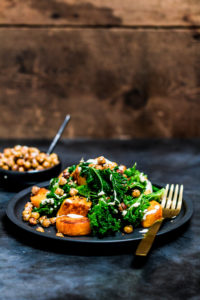 Baked butternut squash cubes with steamed kale, crispy chickpeas and tahini sauce on a black plate