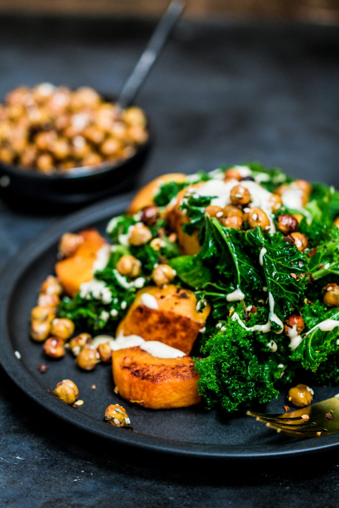 Close up of baked butternut squash cubes with steamed kale, crispy chickpeas and tahini sauce on a black plate