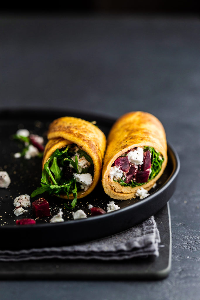 Breakfast egg wraps with goat cheese and beet, on a black plate