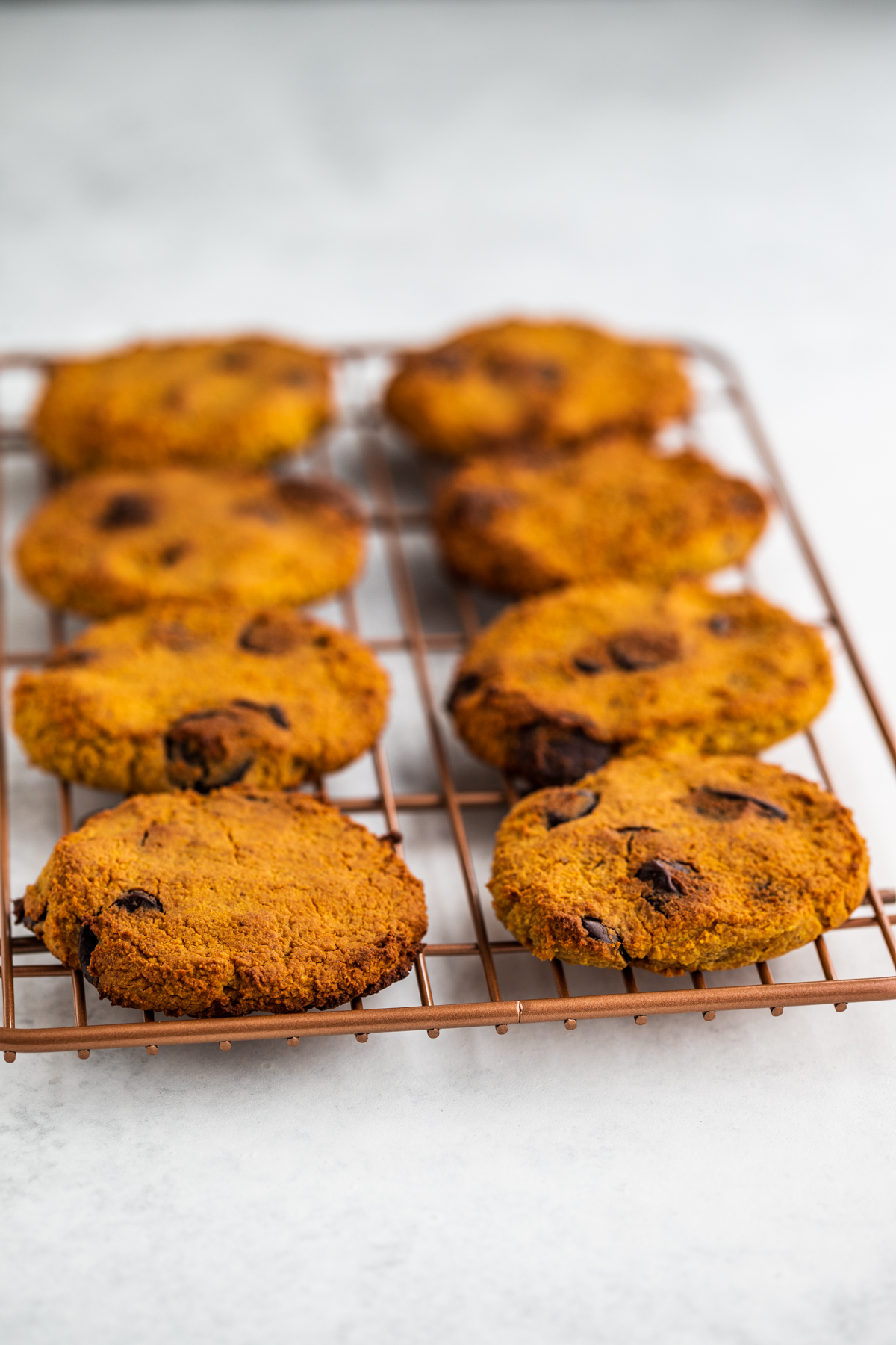 Sweet potato cookies on a rose gold cooling rack on a white background