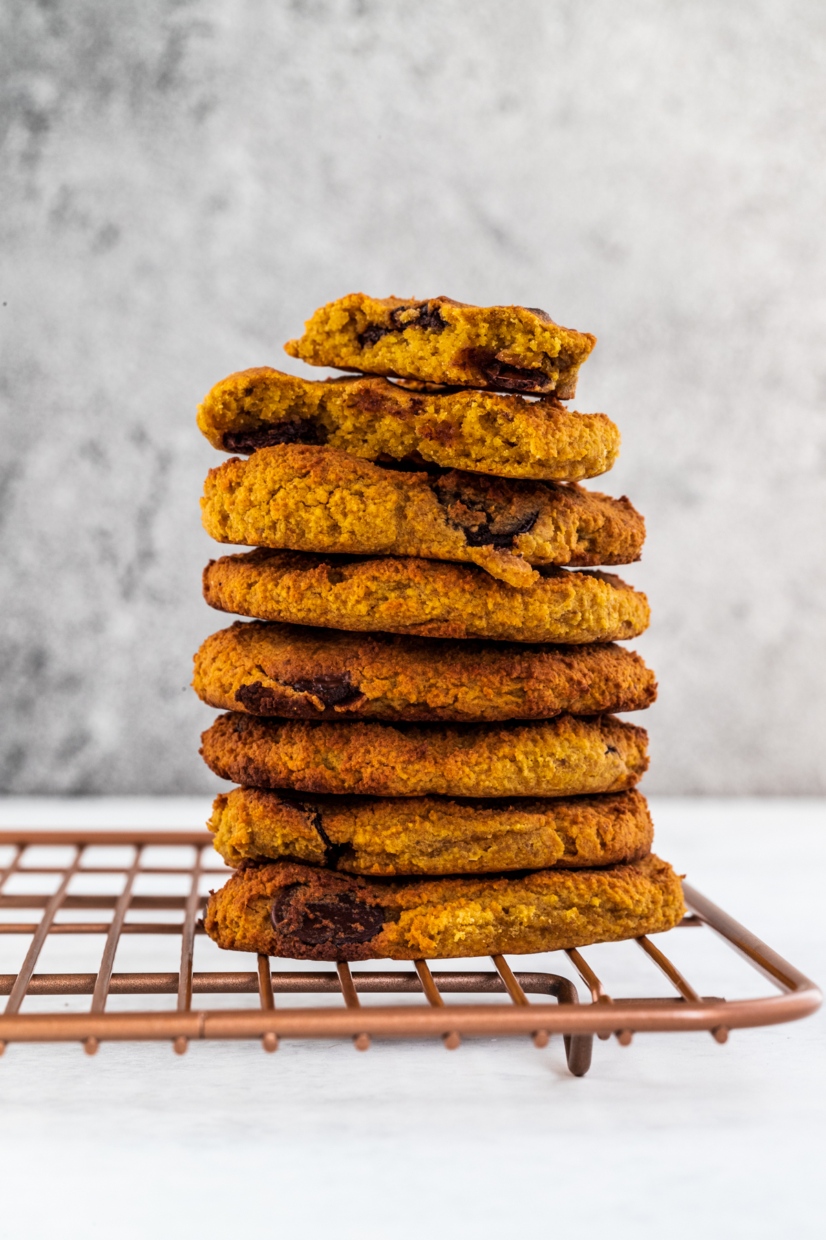 A stack of sweet potato cookies on a rose gold rack and white background