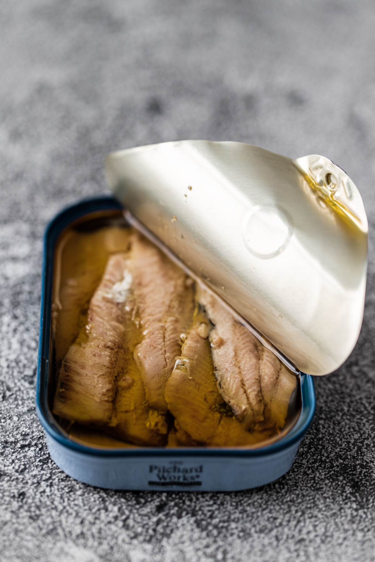 Sardine fillets in a blue tin with the lid half peeled back on a grey black background
