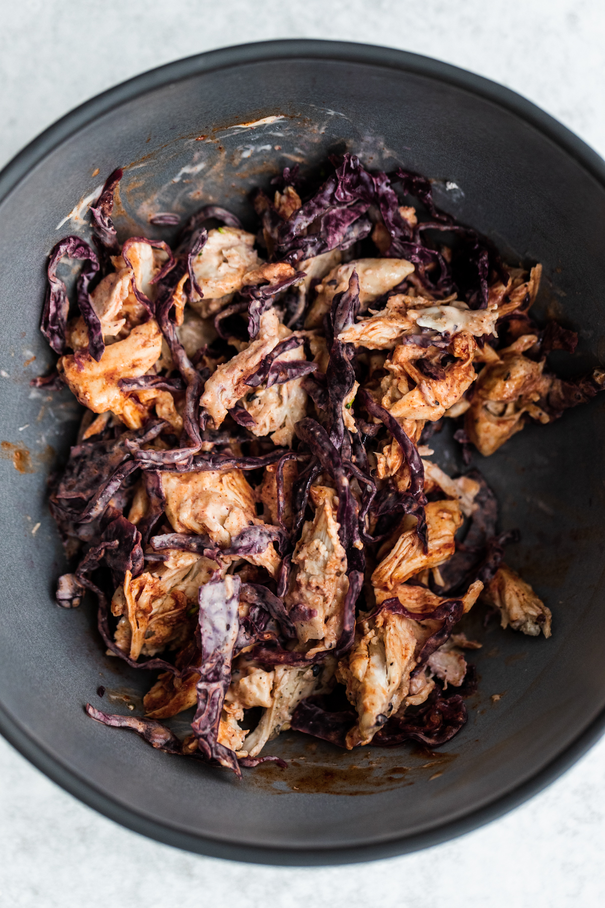 Overhead shot of shredded chicken, red cabbage sauerkraut and hot sauce mayo in a bowl.
