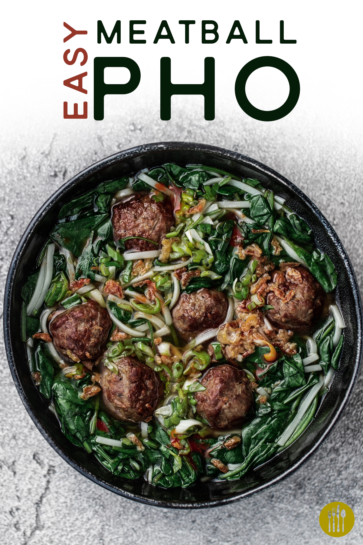A bowl of easy meatball pho in a black bowl on a grey background