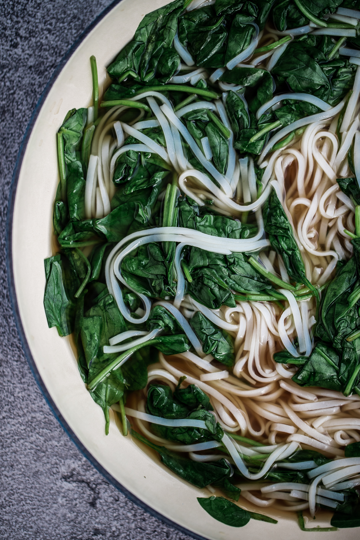 Overhead shot of spinach and white rice noodles in a pan with pho broth