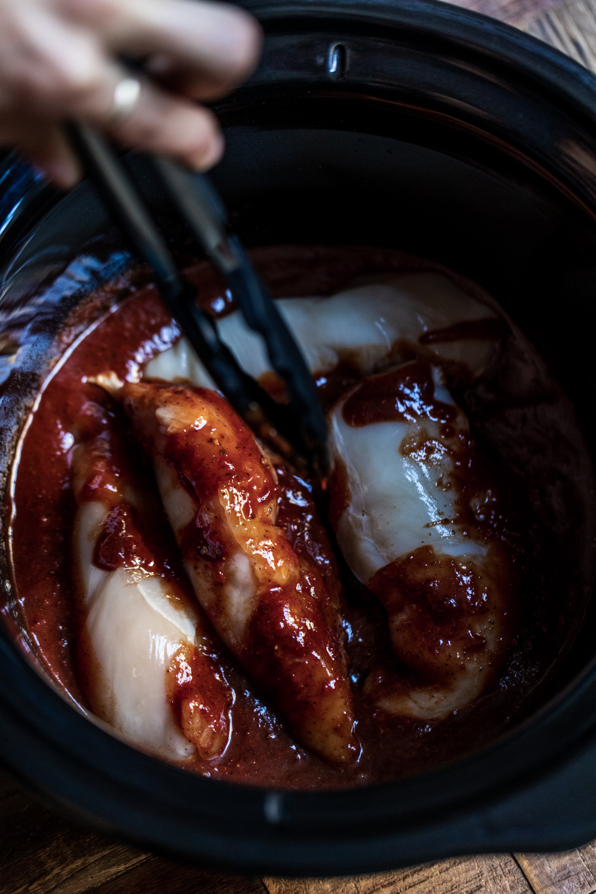 Chicken breasts being put into the chipotle sauce in a slow cooker with tongs