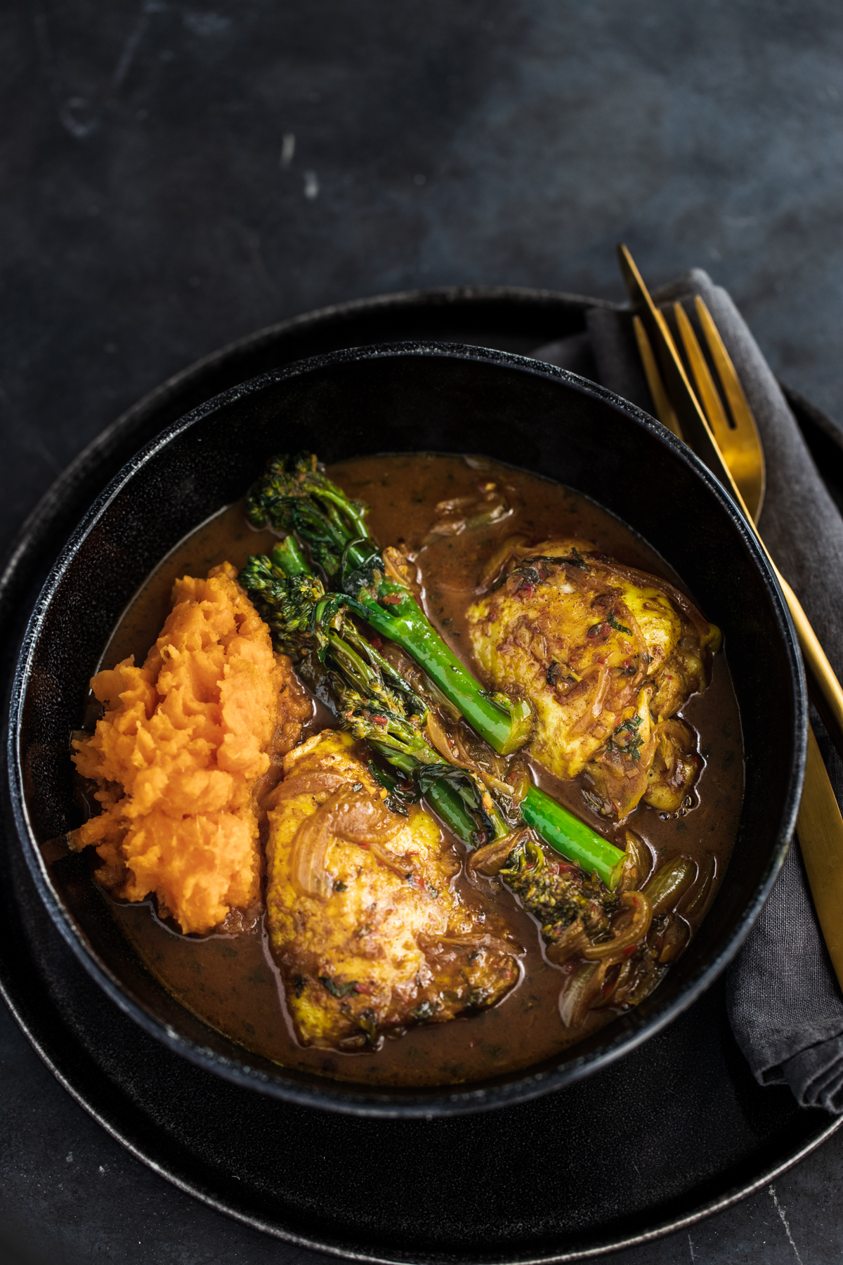 Malaysian Chicken Thigh Curry with broccoli and sweet potato in a black bowl