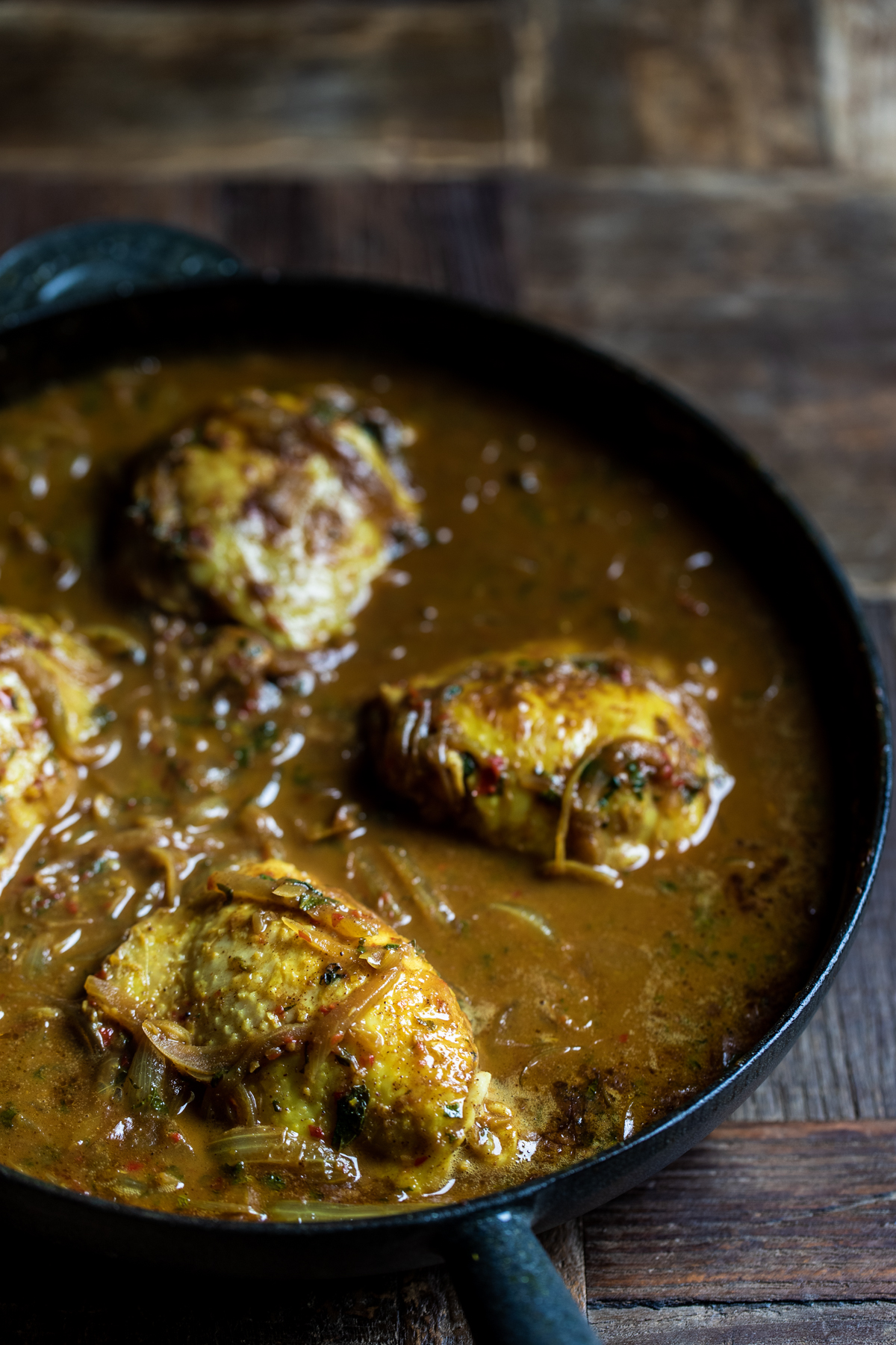 Malaysian chicken thigh curry cooking in a black cast iron pan.