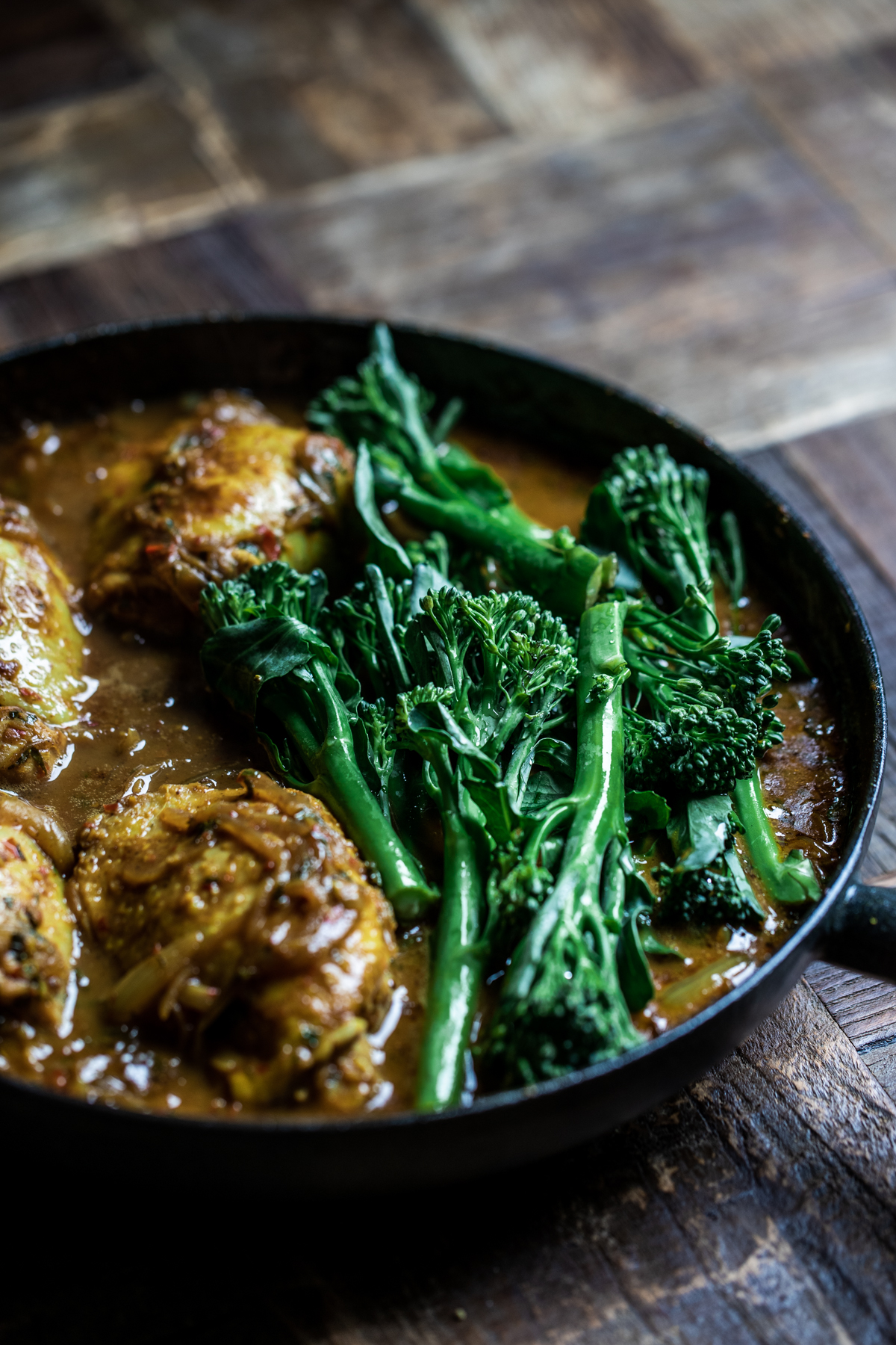Malaysian chicken thigh curry cooking in a black cast iron pan with broccoli.