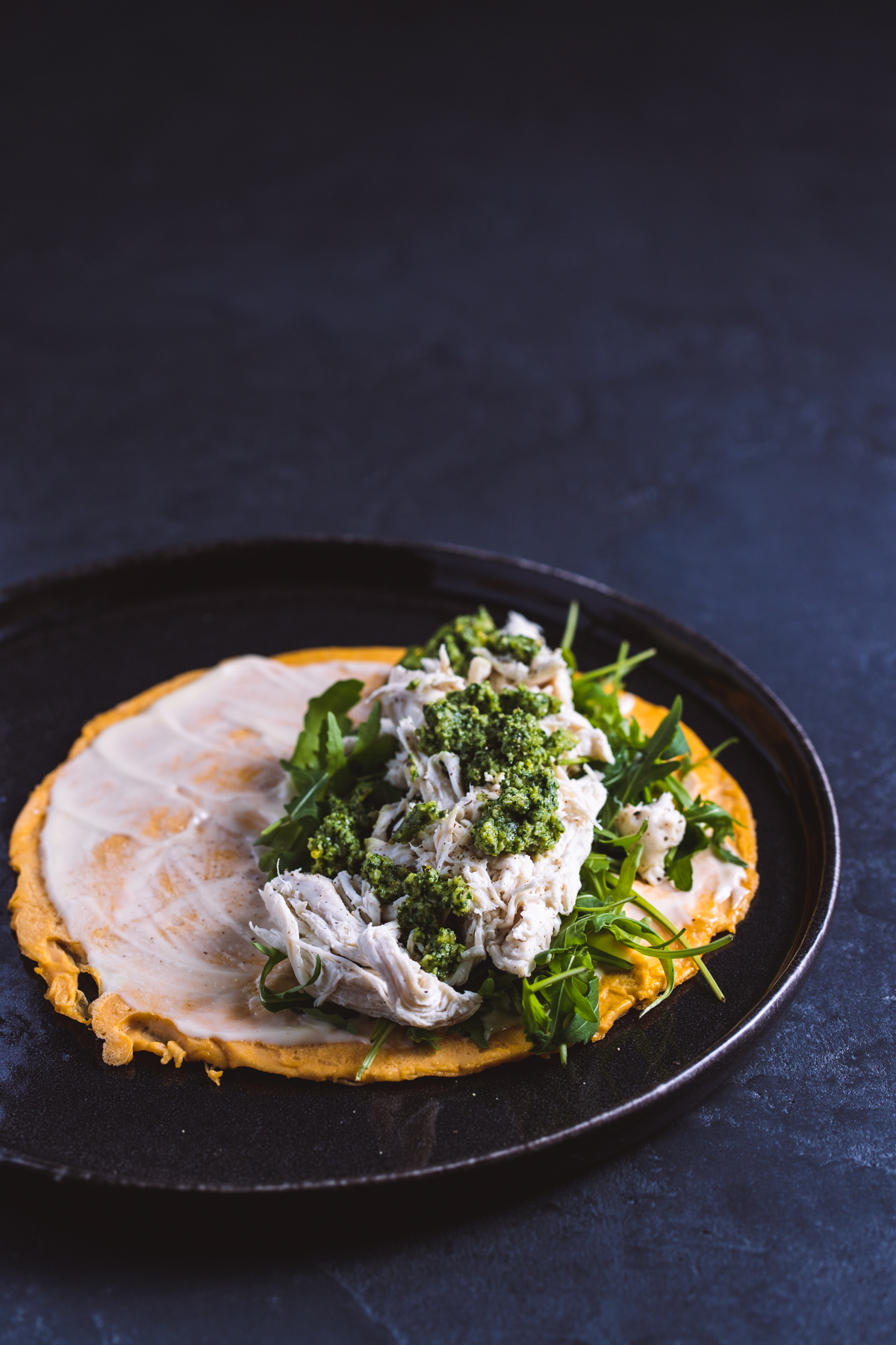 Chicken egg wrap with pesto and rocket on a black plate and black background.