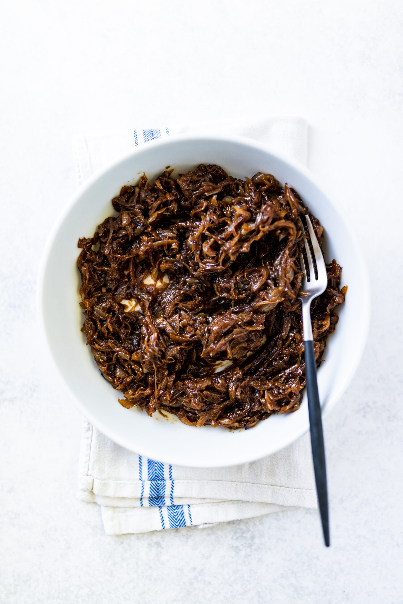 Caramelised onions in a white bowl on a tea towel and white background